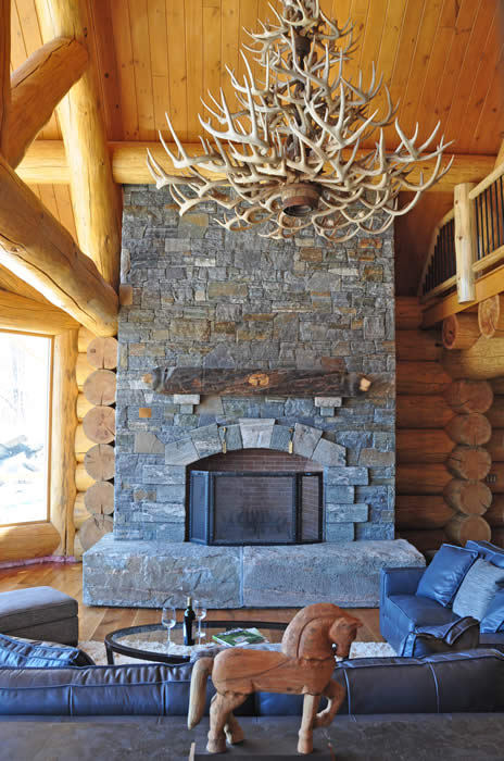 grand fire place with antler chandelier in log home